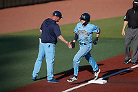 Ryan Teschko (18) of the Old Dominion Monarchs slaps hands with third base coach Chris Finwood after hitting a home run against the Charlotte 49ers at Hayes Stadium on April 25, 2021 in Charlotte, North Carolina. (Brian Westerholt/Four Seam Images)