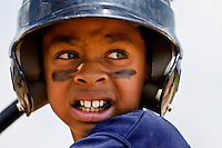 Close up photo of a young baseball player as he is about to take a swing.