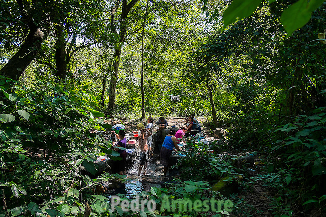 """November 10, 2014. """"Water it´s the real thing""""<br /> A woman comes back from the river where she has been washing the clothes. She doesn' t have water at home. The people of Nejapa in El Salvador, have no drinking water because the Coca -Cola company overexploited the aquifer in the area, the most important source of water in this Central American country. This means that the population has to walk for hours to get water from wells and rivers. The problem is that these rivers and wells are contaminated by discharges that makes Coca- Cola and other factories that are installed in the area. The problem can increase: Coca Cola company has expansion plans, something that communities and NGOs want to stop. To make a liter of Coca Cola are needed 2,4 liters of water. ©Calamar2/ Pedro ARMESTRE"""