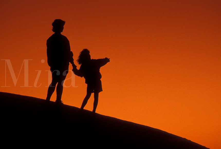 AJ4084, Silhouette, people, overlook, Stone Mountain, Georgia's Stone Mountain Park, Atlanta, Georgia, Silhouette of mother and young daughter holding hands and looking/watching at sunset on the summit of Stone Mountain in Georgia's Stone Mt. Park near Atlanta in the state of Georgia.