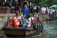 Suzhou, Jiangsu, China.  Chinese Tourists Taking Pleasure Ride on a Canal in Tongli Ancient Town near Suzhou.