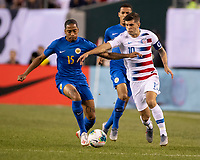 PHILADELPHIA, PA - JUNE 30: Christian Pulisic #10 attacks with the ball and is challenged by Shermaine Martina #15 during a game between Curaçao and USMNT at Lincoln Financial Field on June 30, 2019 in Philadelphia, Pennsylvania.