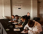 June 13, 2013. Durham, North Carolina<br />  A table was set up for attendees to fill out and print resumes to show to prospective employers. Justin Priest, age 26 (top right), waits for his turn.<br />  JobLink and the city of Durham hosted the Re-Entry Navigation Conference & Job Fair for ex-offenders at the Durham Armory. Those who registered attended a conference on Monday June 10 and then attendees were invited to the job fair on June 13. Although hopes were high for the unemployed, only 5 of the 12 registered companies set up at the fair.