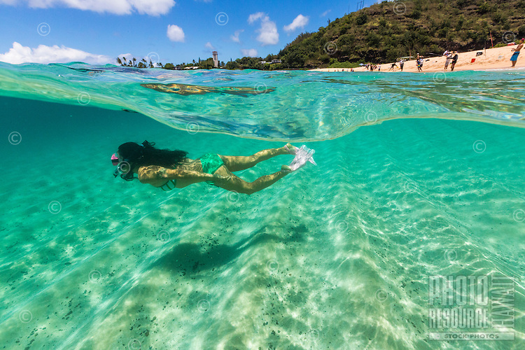 An over-and-under image of a local woman snorkeling at Waimea Bay Beach Park on O'ahu.
