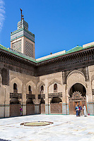 Fes, Morocco.  Medersa Bou Inania.  Tourists with Guide in the interior Courtyard.