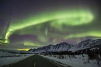 The aurora borealis arc over the Alaska Range and the Richardson Highway in Alaska.