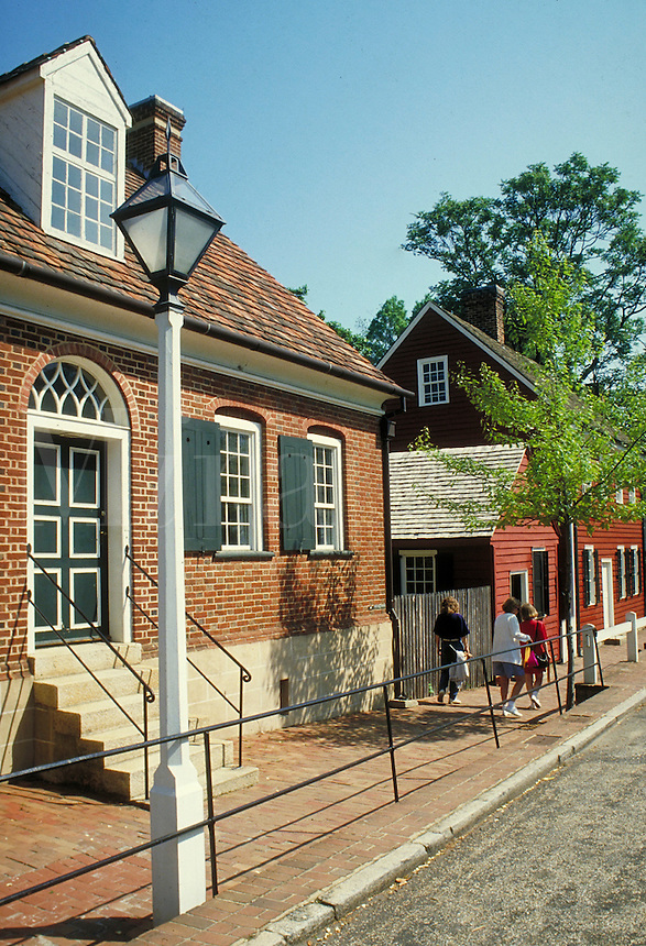 tourists along street in front of historic brick buildings at Old Salem historic site. tourists. Old Salem North Carolina USA.