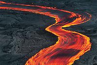 Lava stream near the Pu'u O'o vent in fluid motion through grey rocky landscape