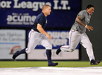 Infielder William Beckwith (48) and outfielder Will Skinner (26) of the Rome Braves race across the tarp during a rain delay before a game against the Greenville Drive on July 5, 2012, at Fluor Field at the West End in Greenville, South Carolina. The game eventually was postponed. (Tom Priddy/Four Seam Images)