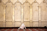 A muslim pilgrim prays at the Umayyad Mosque in the Old City. The mosque is one of the three most significant sites in Islam.