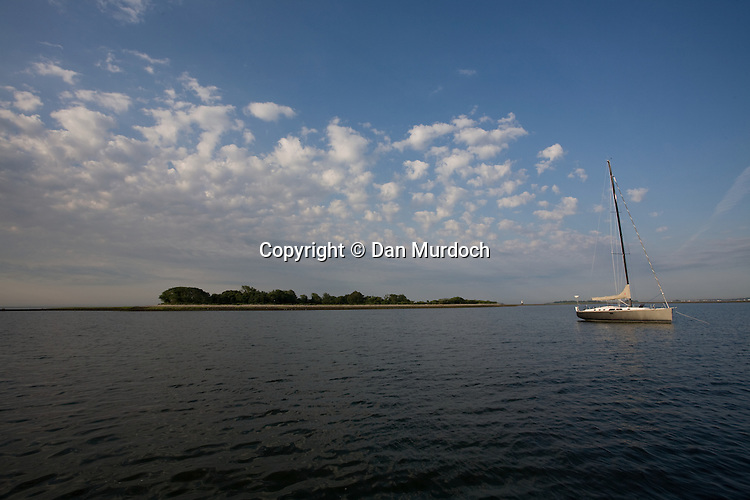 An island under puffy white clouds and sailboat at anchor