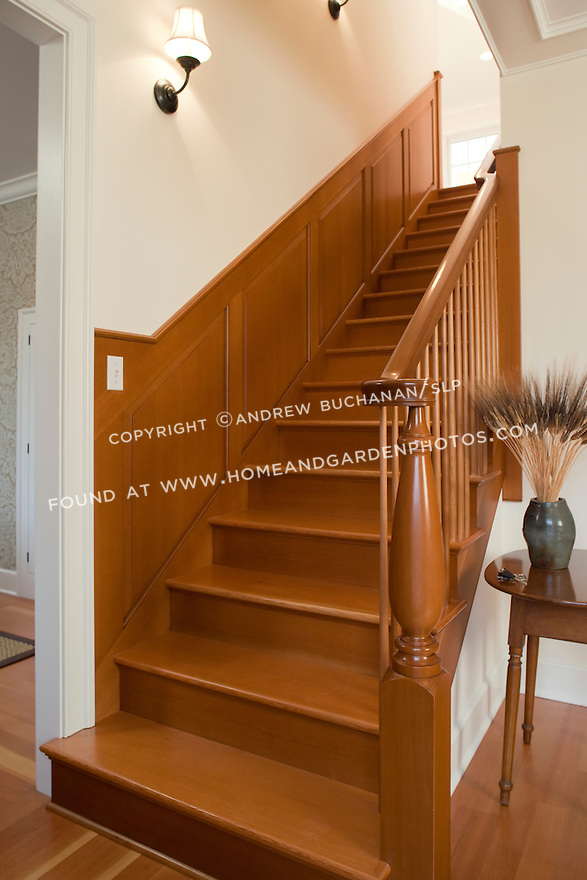 In the entry hall, a straight-ahead sixteen stair flight leads to the second story, cherry treads, risers, ballusters, and wainscotting beautifully finish the staircase, and a newell post turned at a local mill from local fir, all add to the sense of geomoetry, order, and calm of this new contemporary home built in a clean, traditional Shaker style.  The homeowner is a cabinetmaker with a Master's degree in art who designed the house and crafted all of the cabinetry, built-ins, and most other woodwork himself.  The pottery jugs and crocks on the hall table are his work as well.
