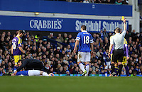 Pictured: Jordi Amat (R obscured) of Swansea sees a yellow card by match refereeKevin Friend (R) for his foul against an Everton player who is being seen to by the team physiotherapist.  Sunday 16 February 2014<br /> Re: FA Cup, Everton v Swansea City FC at Goodison Park, Liverpool, UK.