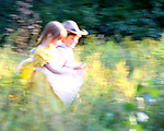 Children running through a field of flowers blurred intentionally