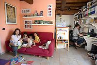 """homeschooling, educazione parentale, educazione domestica.<br /> Erika De Martino con i suoi figli durante una """"lezione"""". Matteo, il padre, al lavoro al computer."""