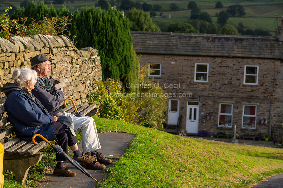 UK, England, Yorkshire, Reeth.  Elderly Couple Relaxing on a Bench, in Late Afternoon Sun.