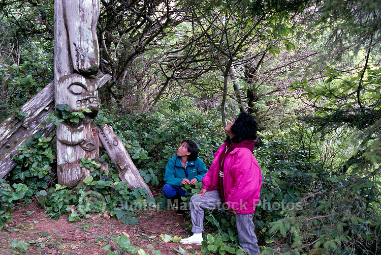 Tourists visiting Nuu-chah-nulth Totem Pole, Acous Peninsula, Kyuquot Sound, off West Coast of Vancouver Island, BC, British Columbia, Canada - Close Up Detail