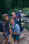 A happy young family resting beside a stream in Rocky Mtns, CO