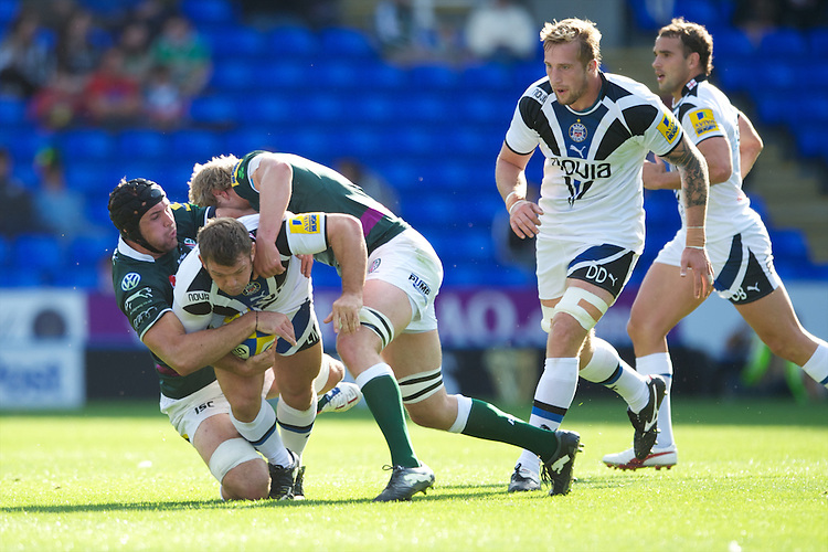 Lee Mears of Bath Rugby is tackled by Matt Garvey (left) and Max Lahiff of London Irish during the Aviva Premiership match between London Irish and Bath Rugby at the Madejski Stadium on Saturday 22nd September 2012 (Photo by Rob Munro)