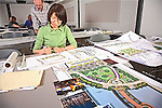 Female Asian adult draws in details on landscape architectural layout designs in classroom on large paper
