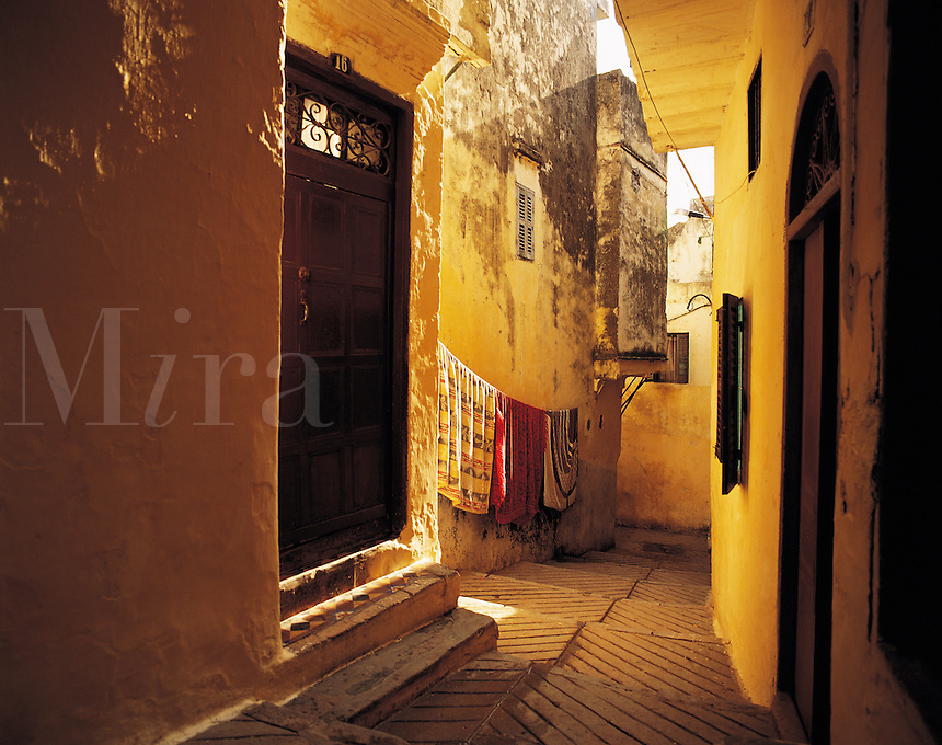 Narrow lane painted in bright reds and yellows, with doorways, brightly-coloured washing, interesting patterns, Tangiers, Morocc