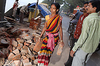 A woman carries bricks on a worksite in central Kolkata.<br />