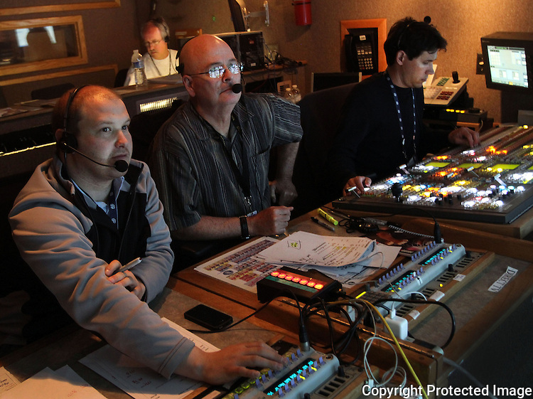 In the Fox TV production trailer at Petco Park, from right, technical director, Tom Connole, director Michael Oddino and producer Max Michalak work at a bank of TV monitors during a Padre Game in 2012. photo for The Californian
