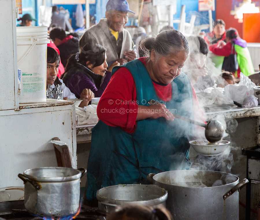 Peru, Cusco, San Pedro Market.  Cook Serving Food for a Customer in the Food Court Area of the Market.