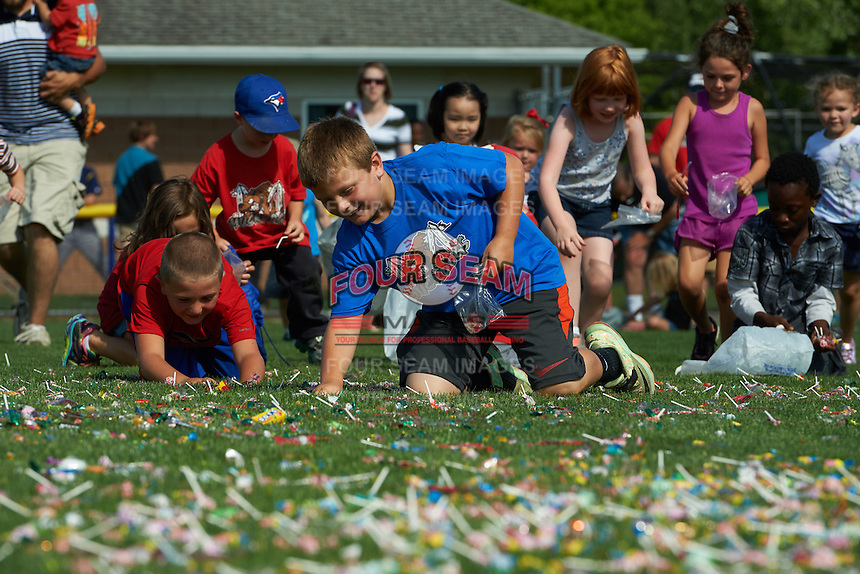 Batavia Muckdogs young fans pick up candy after a helicopter dropped it into the outfield after a game against the State College Spikes August 23, 2015 at Dwyer Stadium in Batavia, New York.  State College defeated Batavia 8-2.  (Mike Janes/Four Seam Images)