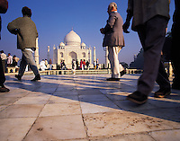 Low-angle view of the Taj Mahal with crowds of visitors, some walking briskly past in the foreground; Agra, Indi