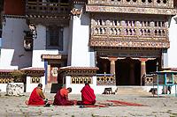 Phobjikha, Bhutan.  Buddhist Monks Sitting in Courtyard of  Gangte Monastery (Goemba).