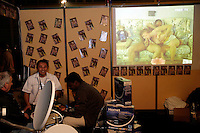 Switzerland. Geneva. Extasia 05 is the first erotic and sex fair. An asiatic man laughs on the stand of a porn television by satellite dish (digital satellite receiver).  A porn film is shown on the screen. The woman is making a blowjob to the man.  © 2005 Didier Ruef
