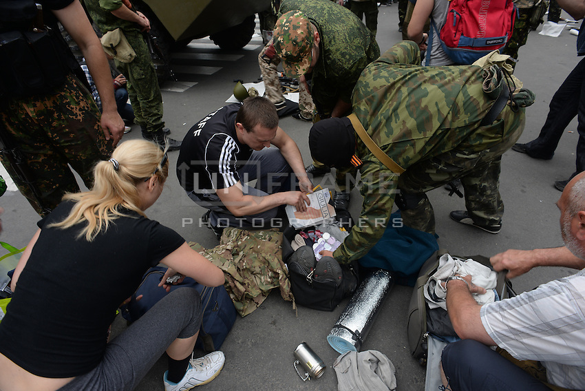 """Members of special pro-Russian batalion """"Vostok"""" check personal belongings of workers of town hall during the military coup in DNR (Donetsk Peoples Republic), taking over town hall, held by another group of pro-russian activists."""