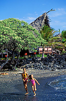 Two girls running and playing on black sand beach on the ocean shore in front of Kona village resort on the Big island of Hawaii