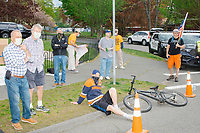 """People watch as people gather for an anti-lockdown protest organized by the alt-right group Super Happy Fun America near the home of Massachusetts governor Charlie Baker in Swampscott, Massachusetts, on Sat., May 16, 2020. The protest was in defiance of Massachusetts orders mandating face coverings and social distancing and prohibiting gatherings larger than 10 people during the ongoing Coronavirus (COVID-19) global pandemic. The state's stay-at-home order is expected to be updated on May 18, 2020, with a phased reopening plan issued by the governor as COVID-19 cases continue to decrease. Anti-lockdown protests such as this have become a conservative cause and have been celebrated by US president Donald Trump. Many of the protestors displayed pro-Trump messages or wore Trump campaign hats and shirts with phrases including """"Trump 2020"""" and """"Keep America Great."""" Super Happy Fun America, organizers of the protest, are an alt-right organization best known for creating the 2019 Boston Straight Pride Parade."""