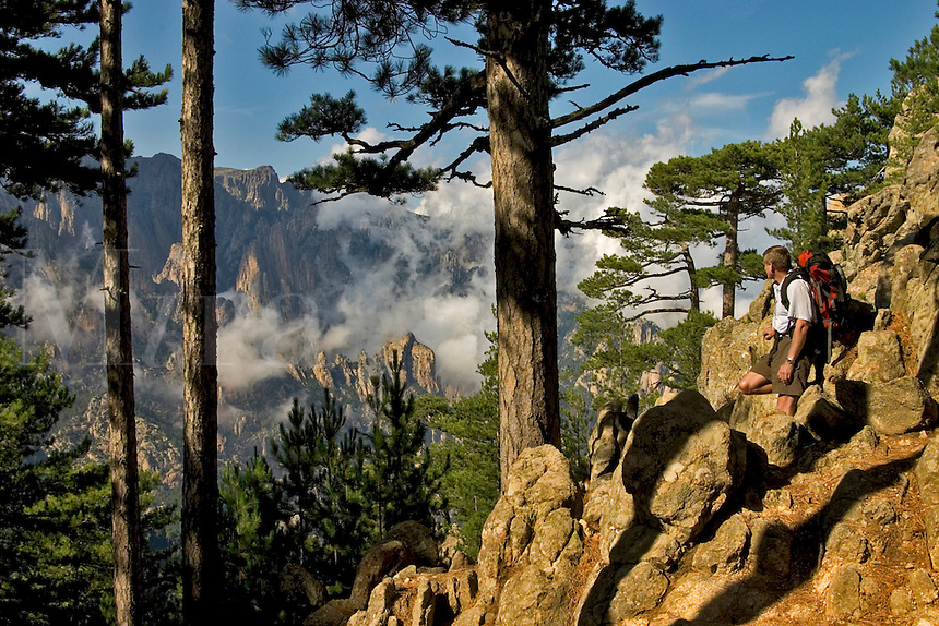 Corsica. Punta Aracale, looking across the valley towards Aiguilles de Bavella. France. Corse. Walker with backpack on the GR20..