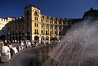 Germany, Munich, Bavaria, Munchen, Europe, People sitting around the fountain in the public plaza in downtown Munich.