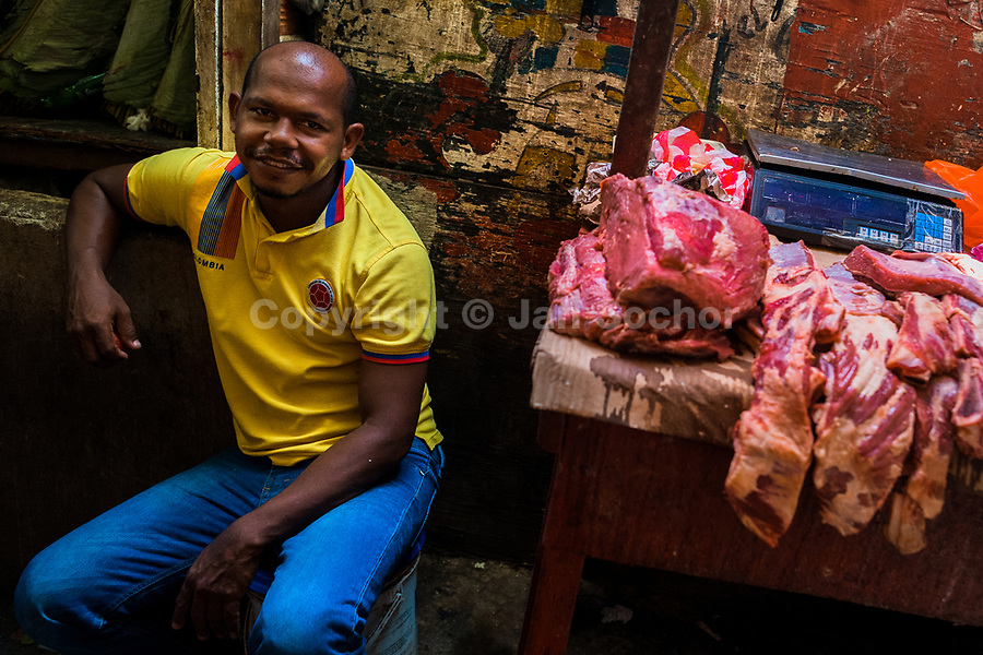 An Afro-Colombian butcher waits for customers in his stand in the market of Bazurto in Cartagena, Colombia, 12 December 2017. Far from the touristy places in the walled city, a colorful, vibrant labyrinth of Cartagena's biggest open-air market sprawls to the Caribbean seashore. Here, in the dark and narrow alleys, full of scrappy stalls selling fruit, vegetables and herbs, meat and raw fish, with smelly garbage on the floor and loud reggaeton music in the air, the African roots of Colombia are manifested.