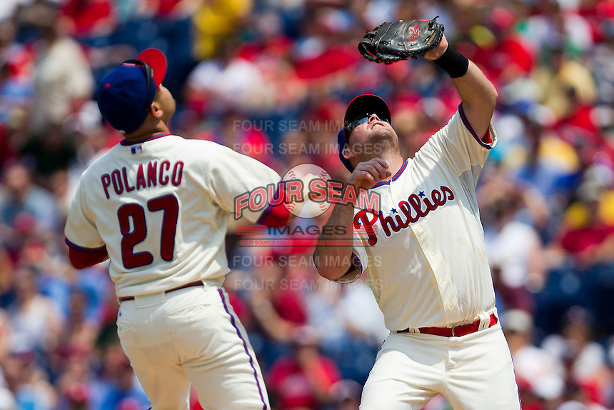 Philadelphia Phillies first baseman Ty Wigginton #24 tracks an infield pop up while teammate Placido Polanco #27 watches during the Major League Baseball game against the Pittsburgh Pirates on June 28, 2012 at Citizens Bank Park in Philadelphia, Pennsylvania. The Pirates defeated the Phillies 5-4. (Andrew Woolley/Four Seam Images).