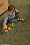 16 month old toddler boy playing with blocks making block tower