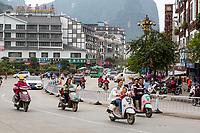 Yangshuo, China.  Street Scene, Traffic, Motorbikes, No helmets.