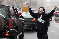 Moscow, Russia, 26/02/2012..An opposition protester waves to passing cars as tens of thousands of people formed a 16-kilometre [10-mile] human chain along Moscow's Garden Ring Road in the latest protest against Prime Minister Vladimir Putin and his presidential election campaign. Opposition activists estimated that they needed 34,000 people to complete the chain and symbolically encircle central Moscow.