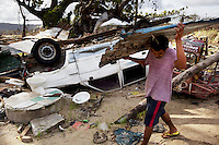 Philippines. Province Eastern Samar. Hernani. A man collects and recycles corrugated iron sheet to build a makeshift shelter. An upside down car and tricycle, the rubbles of a private house's toilet and toilet seat, all destroyed by typhoon Haiyan's winds and storm surge. 95 % of the town was destroyed by typhoon Haiyan. Typhoon Haiyan, known as Typhoon Yolanda in the Philippines, was an exceptionally powerful tropical cyclone that devastated the Philippines. Haiyan is also the strongest storm recorded at landfall in terms of wind speed. Typhoon Haiyan's casualties and destructions occured during a powerful storm surge, an offshore rise of water associated with a low pressure weather system. Storm surges are caused primarily by high winds pushing on the ocean's surface. The wind causes the water to pile up higher than the ordinary sea level. 26.11.13 © 2013 Didier Ruef