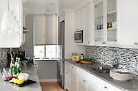 Open plan kitchen with white cupboards