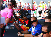 Sep 13, 2013; Charlotte, NC, USA; A female fan leans in for an autograph from NHRA top fuel dragster driver Antron Brown while Brandon Bernstein throws a photo bomb during qualifying for the Carolina Nationals at zMax Dragway. Mandatory Credit: Mark J. Rebilas-