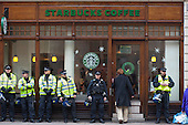 Police guard a branch of Starbucks during a National Campaign against Fees and Cuts march through the City of London.