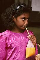 """Asie/Malaisie/Kuala Lumpur: Chinatown - Jeune fille buvant du jus de fruits dans un sachet sur le marché """"Chowkit"""""""