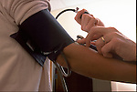 hands taking blood pressure test on patient