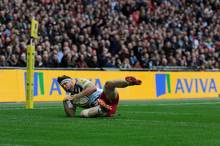 Jack Clifford of Harlequins scores an early try after charging down the clearance kick of Neil de Kock of Saracens