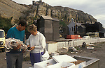 Hastings East Sussex,  fisherman sells locally caught fish wrapped in newspaper to woman. Note vernacular railway.  1980s.